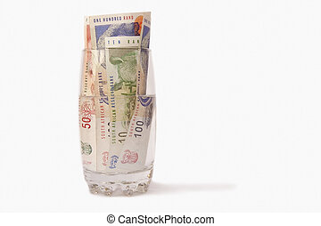 Money and water - South African money in a glass of water,...
