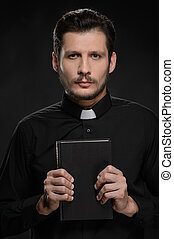 Priest with the Holy Bible. - Portrait of priest holding the...
