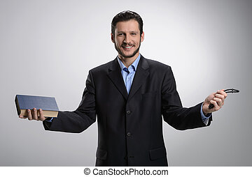 Religious businessman. Cheerful bearded man in formalwear holding the Holy Bible and rosary beads in his hands while isolated on grey