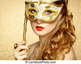 Beautiful young woman in mysterious golden Venetian mask....