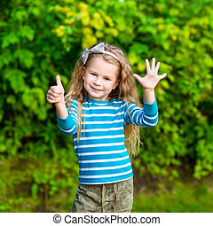 Cute blond little girl with long curly hair showing six...