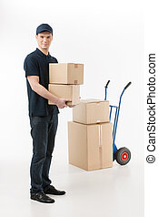 Moving boxes. Full length of young deliveryman holding a stack of boxes with a hand truck on the background