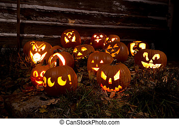 Jack-O-Lanterns Carved for Halloween Lit in Orange in Grass...