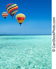 Hot air balloons travel over the sea - Colorful hot air...