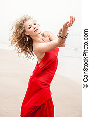 woman on sea beach in foggy day - Beautiful woman in red...