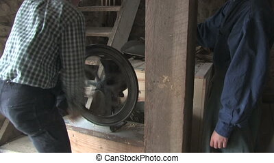 Grinding Corn on the Farm - Two people pulverize corn in a...
