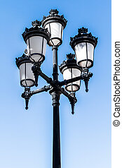 Old street light or lamp post lantern on a blue sky...