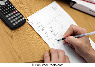 Doing Math Homework - A young man working out mathematical...