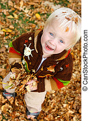 Baby Playing Outside in Falling Leaves - a cute, happy young...