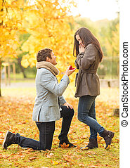 man proposing to a woman in the autumn park - holidays,...