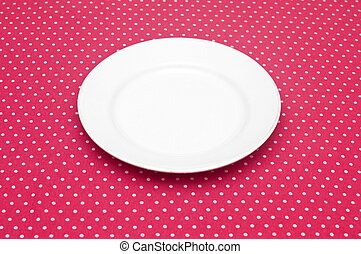 Empty white dinner plate on fun red polka dot tablecloth.