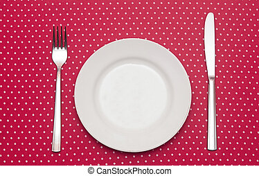 Empty white dinner plate with utensils on fun red polka dot...