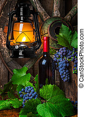 A bottle of red wine on the background of grapes - Bottle of...