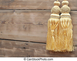 Gold curtain tassel against wooden wall