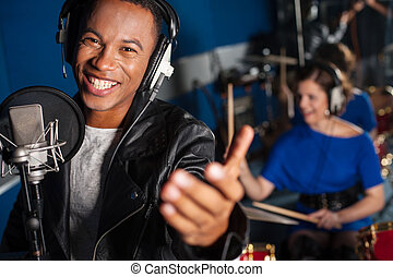 Young man singing in studio - Male singer recording a song...