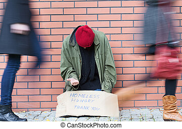 Homelessness in a big city - Homeless man sitting on a...