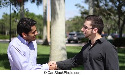 Two businessmen chat outdoors