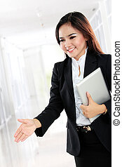 Attractive businesswoman with an open hand ready for handshake
