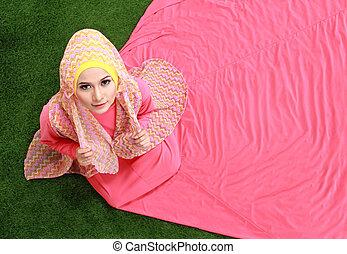 Young muslim girl sitting on grass - Young muslim girl...