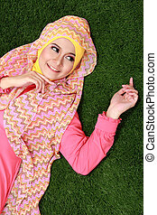 Young muslim girl lying on grass