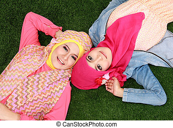 two muslim woman lying on grass - two beautiful happy muslim...