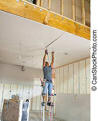 Drilling the Sheetrock - Worker on stilts drilling the...