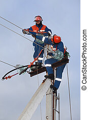 Two electrics working on top of an electricity pylon
