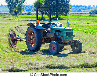 Old Tractor - Old green tractor with harrow wheel on a field