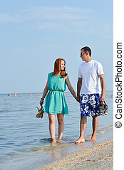 Young happy couple walking holding hands on seashore
