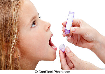 Young girl taking homeopathic medicine - Young girl taking...