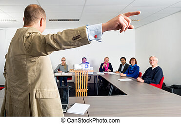 Entrepreneur Giving Presentation To Colleagues - Male...