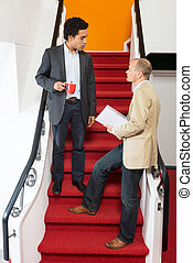 Businessmen Discussing On Steps - Businessmen discussing on...