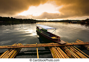 Sunrise over dam at port and fishing boat in Kanchanaburi...