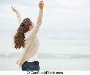 Happy young woman in sweater rejoicing on beach rear view