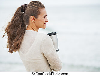 Happy young woman in sweater on beach with cup of hot...