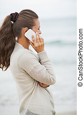 Young woman in sweater on beach talking cell phone