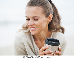 Portrait of happy young woman in sweater sitting on lonely...