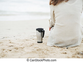 Closeup on cup of hot beverage near young woman in sweater...