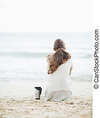 Cup of hot beverage near young woman in sweater sitting on...