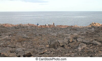 Man fishing on a cliff - A wide shot of men sitting on the...