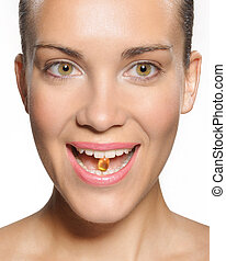 Smiling woman with pill in teeth