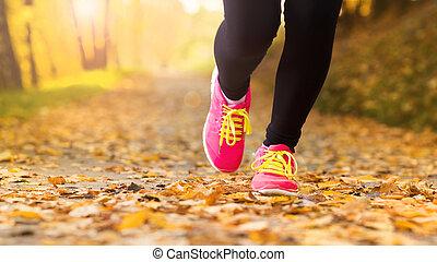 Runner - Close up of feet of a runner running in autumn...