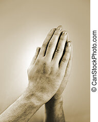 Prayer - Sepia toned photograph of hand clasped in prayer