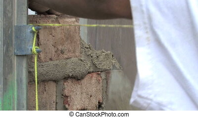 Laying Brick 1 - Hands laying brick and mortar on a house...