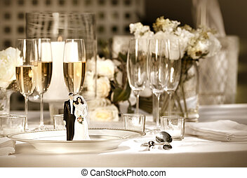 Cake figurines on dinner plate at wedding reception