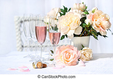 Two glasses filled with pink Champagne with flowers