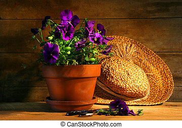 Purple pansies with old straw hat on a rustic table