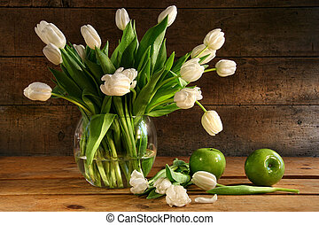 White tulips in glass vase on rustic wood