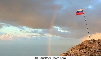 Russian flag on the top of a mountain on the background of...