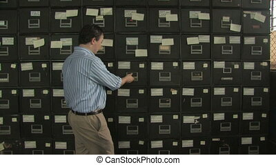 Man at File Cabinet 1 - A man enters the frame and searches...